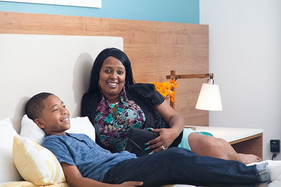 A mother and her son relaxing on a bed inside an InTown Suites Extended Stay.