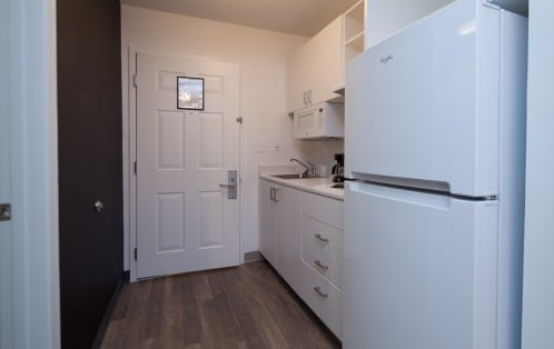 A kitchenette with white cabinets, white appliances and dark wood floors.