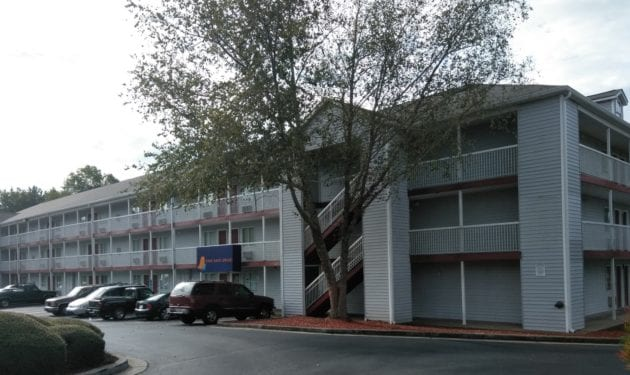 Exterior of InTown Suites property with a big tree in the front and cars in the front on a cloudy day,